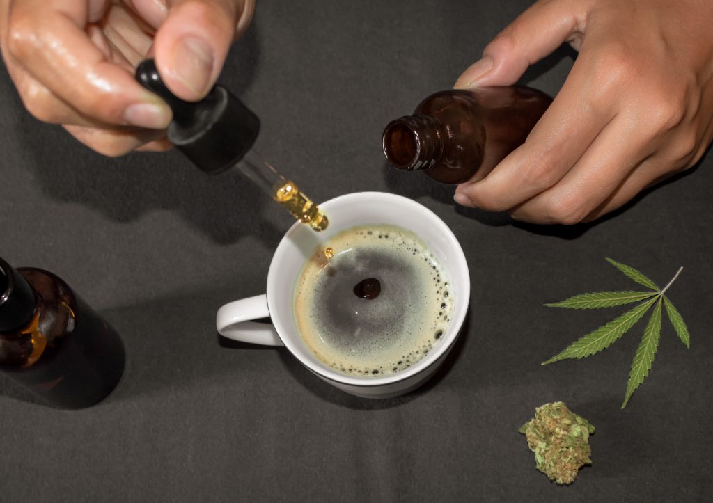 CBD Consumption Forms Pouring CBD tincture in a coffee cup, natural remedy of marihuana. Person using cannabis oil with a dropper in a table with marihuana leaf. CBD Consumption Forms